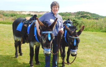 Volunteer holding donkeys outside the Sand Bothy at the RNLI fun day event