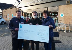 Three people holding giant cheque outside Balmedie Co-op store